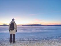 Kobieta w ciepłym długim kurtka pobycie na piaskowatej plaży przy zamarzniętym jeziorem zdjęcia stock