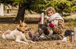 Kobieta w ciepłym szaliku cieszy się pinkin z jej psem w parku w jesieni Obraz Royalty Free