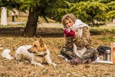 Kobieta w ciepłym szaliku cieszy się pinkin z jej psem w parku w jesieni Fotografia Stock