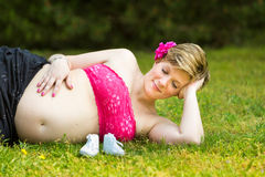 Kobieta w ciąży lying on the beach w zielonej trawie Obraz Stock