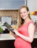 Kobieta w ciąży używa pastylka komputer w kuchni Obraz Stock