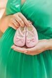 Kobieta w ciąży w zieleni sukni brzucha mienia menchii dziecka łupach, e Obrazy Royalty Free