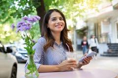 Kobieta w cukiernianej pije kawie, trzymający telefon i patrzejący kamerę kosmos kopii fotografia stock
