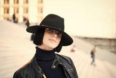 Kobieta w czarnego kapeluszu i kurtki pozie na schodkach obrazy royalty free