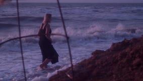 Kobieta w czarnej sukni chodzi na plaży w wodzie morskiej, fale, piana Przepustki kamieniami ziemia, glina zbiory