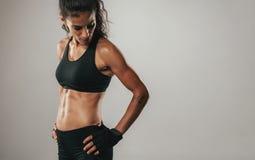 Kobieta w czarnych sportowych wierzchołków spojrzeniach nad ramieniem Obraz Royalty Free