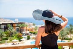 Kobieta w czarnym kapeluszu przy kurortem Zdjęcia Royalty Free