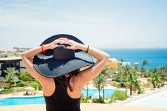 Kobieta w czarnym kapeluszu przy kurortem Zdjęcie Royalty Free