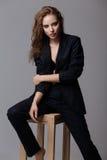 Kobieta w czarnym kostiumu siedzi na krześle Obraz Royalty Free