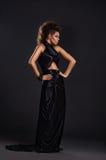 Kobieta w czerń długiej sukni nad ciemnym tłem Zdjęcie Royalty Free