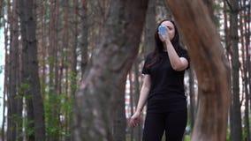 Kobieta w czerni bawi się ubiór w drewnach lub parka, woda pitna od butelki po bieg zbiory wideo