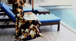 Kobieta w czerni spódnicy sukni słomianym kapeluszu siedzi krzesła obrazy stock