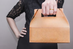 Kobieta w czerni sukni stał z rękami akimbo i przynoszą przekąski pudełko Zdjęcia Stock