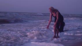 Kobieta w czerni sukni stoi na kamieniu w falach, piana, lato, wieczór zbiory