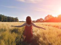 Kobieta w czerwieni smokingowej cieszy się naturze świetle słonecznym w słomy polu i Zdjęcie Royalty Free