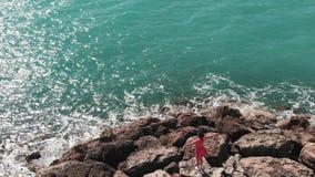 Kobieta w czerwieni smokingowym cieszy się słońcu i grże wiatrową pozycję na skałach na dennym molu z rękami w oddaleniu Widok z  zbiory
