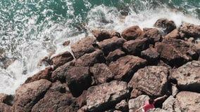 Kobieta w czerwieni sukni pozycji na skalistej falezie z rękami w oddaleniu z błękitne wody ciupnięciem przeciw skalistej molo pl zbiory