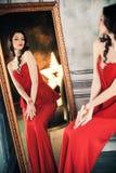 Kobieta w czerwieni sukni przed lustrem Zdjęcia Stock