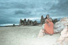 Kobieta w czerwieni sukni przy plażą z ciemnymi burz chmurami Zdjęcie Stock