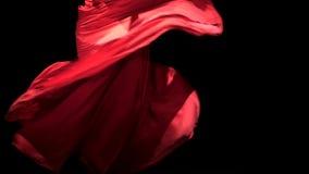 Kobieta w czerwieni sukni wykonuje eleganckich ruchy z jej rękami w tanu Czarny tło z bliska zbiory