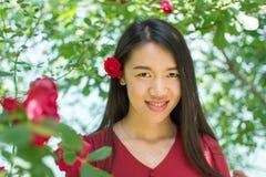 Kobieta w czerwieni sukni z czerwieni różą w jej włosy Fotografia Royalty Free