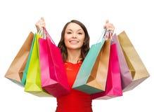 Kobieta w czerwieni sukni z kolorowymi torba na zakupy Zdjęcia Royalty Free