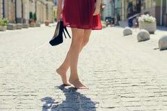 Kobieta w czerwonej eleganckiej sukni, trzyma szpilki buty w ręce i Fotografia Stock