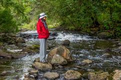 Kobieta w czerwonej kurtce rzeką Zdjęcia Stock