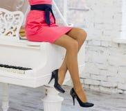 Kobieta w czerwonej sukni na białym pianinie Obrazy Stock