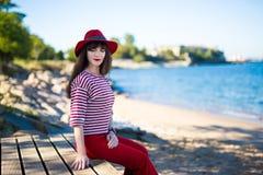 Kobieta w czerwonym obsiadaniu na plaży Obrazy Royalty Free