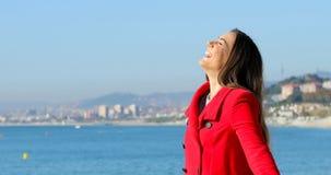 Kobieta w czerwonym oddychania świeżym powietrzu w zimie na plaży zbiory