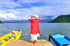 Kobieta w czerwonym trwanie molu jeziorem Zdjęcie Royalty Free
