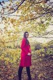 Kobieta w długim czerwonym żakiecie w lasowym kręceniu w kierunku ciebie obrazy royalty free
