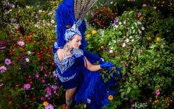 Kobieta w drogiej egzotycznej karnawałowej kostium pozie w łące kwiaty. Zdjęcie Stock