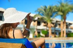Kobieta w dużym białym kapeluszowym lying on the beach na lounger blisko basenu przy hotelem, pojęcia lata czas podróżować w Egip zdjęcia royalty free