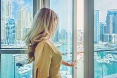 Kobieta w Dubaj Marina, Zjednoczone Emiraty Arabskie Atrakcyjna dama jest ubranym d?ug? sukni? podziwia Marina ?wiat?a dziennego  zdjęcie stock