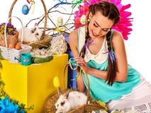 Kobieta w Easter stylu mienia kwiatach w koszu i króliku Zdjęcia Royalty Free