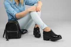 Kobieta w eleganckich butach z eleganckim plecakiem na popielatym tle obrazy royalty free