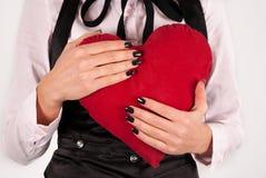 Kobieta w eleganckich płótnach i krawat ściskamy dużą czerwoną kierową poduszkę Obrazy Stock