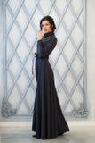 Kobieta w eleganckiej długiej sukni w studiu luz zdjęcie royalty free