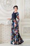 Kobieta w eleganckiej kolorowej długiej sukni w studiu luz zdjęcia royalty free