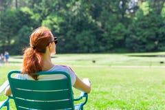 Kobieta w eyeglasses relaksuje na greenfield obrazy stock