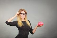 Kobieta w eyeglasses wprawiać w zakłopotanie trzymający mózg Zdjęcie Stock