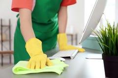 Kobieta w fartuchu i rękawiczkach czyści biuro zdjęcie stock