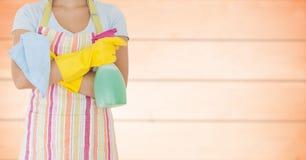 Kobieta w fartuchu z rękami składać przeciw rozmytemu pomarańczowemu drewnianemu panelowi i cleaner obraz stock