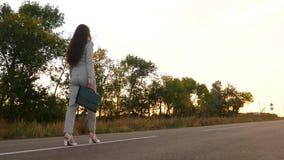 Kobieta w garniturze z czarną teczką w jej ręce chodzi wzdłuż drogi zdjęcie wideo