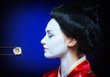 Kobieta w gejszy makeup łasowania suszi zdjęcia royalty free