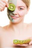 Kobieta w gliny masce na twarzy nakrycia oku z kiwi zdjęcia stock