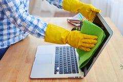 Kobieta w gumowych rękawiczkach czyści z kwacza pokazem laptop Obrazy Royalty Free