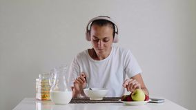 Kobieta w hełmofonach jest słuchającym muzyką podczas gdy jedzący cornflakes z mlekiem zbiory